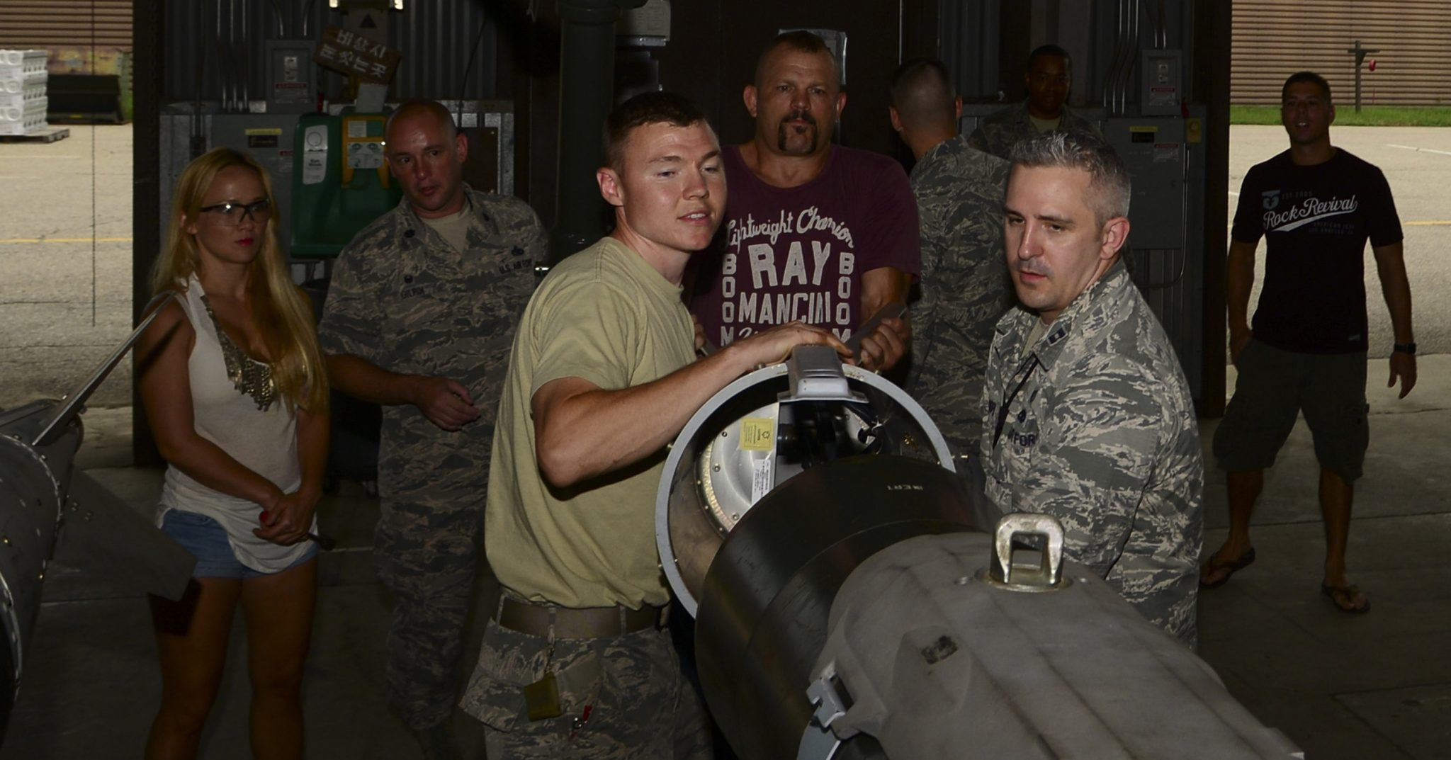 """Staff Sgt. Layne Short, 51st Munitions Squadron flightline maintenance munitions inspector, Chuck """"The Iceman"""" Liddell, retired American mixed martial artist, and Capt. Andrew Cooper, 51st MUNS munitions operations officer, assemble a guided bomb unit-31 on Osan Air Base, South Korea, Aug. 5, 2015. Liddell and his family visited various Osan units during a morale trip Aug. 2 – 5. (U.S. Air Force photo/Senior Airman Kristin High)"""