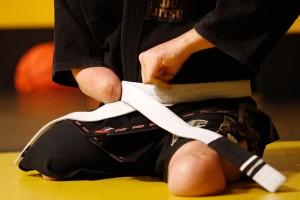 Joey Bozik ties his belt as he prepares for a Brazilian jiu-jitsu training sesson.