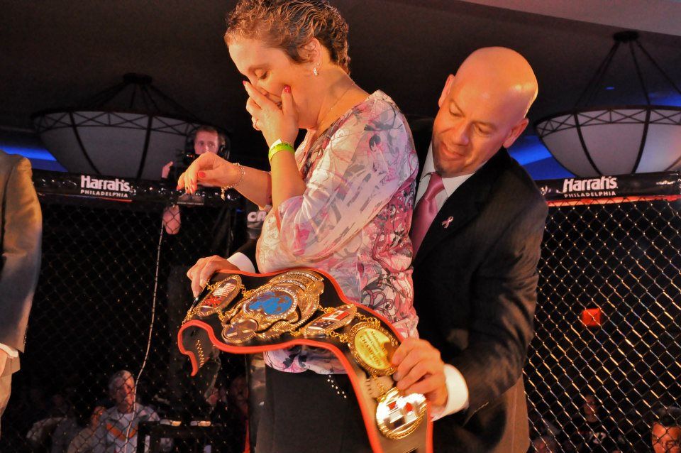 "Bob Meloni wraps a ""Breast Cancer Survivor"" Championship belt around his wife Marlene's waist"