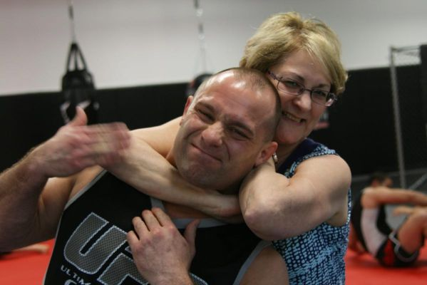 Janice Serra, right, playfully puts her son, Matt, a former UFC welterweight champion, in a rear naked choke submission hold at his new Serra BJJ Academy in Huntington. (May 5, 2010) Photo Credit: Jenny Patten